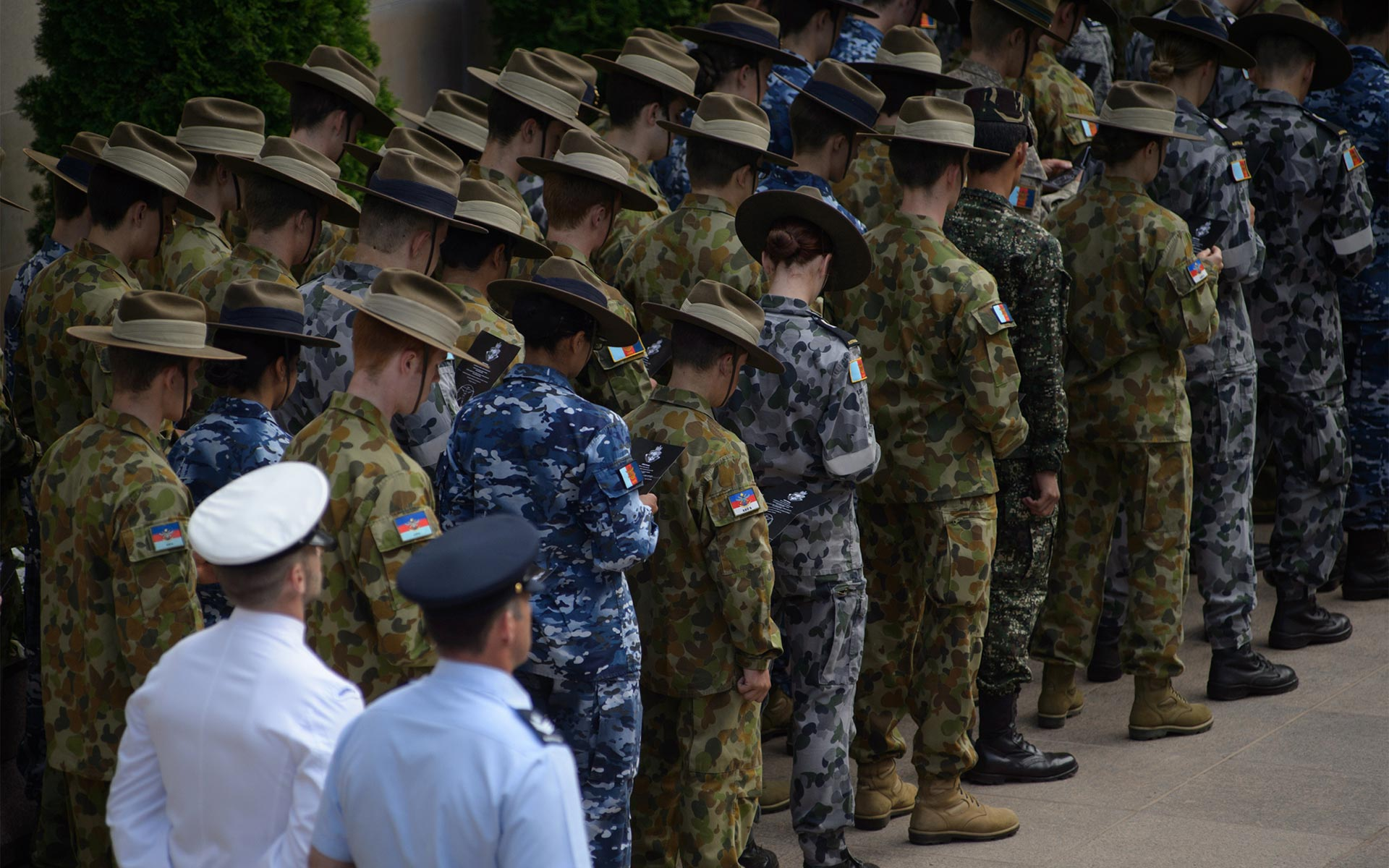 ADF personnel with heads bowed