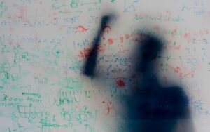 Translucent whiteboard covered in equations and scribbles